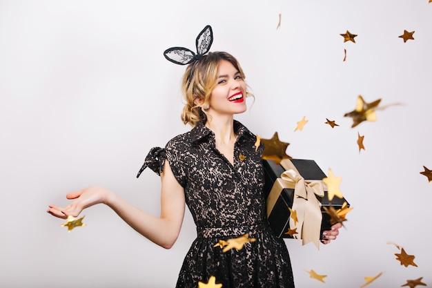 Gelukkige tijd, jonge lachende vrouw met geschenkdoos vieren, zwarte jurk en kroon dragen, gelukkige verjaardagsfeestje, sprankelende gouden confetti, plezier maken, glimlachen.