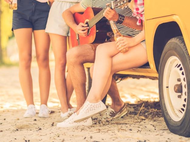 Gelukkige tijd met vrienden. close-up van een groep jonge mensen die samen tijd doorbrengen in de buurt van hun minibus terwijl een man gitaar speelt playing