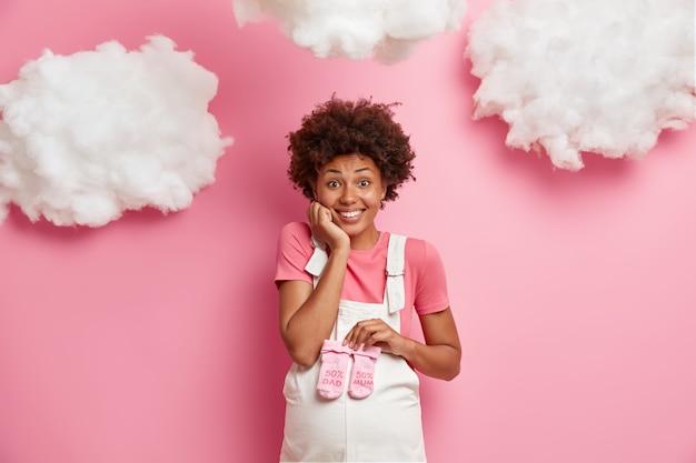 Gelukkige toekomstige moeder verwacht baby, houdt roze kindersokken vast over buik, gekleed in denim overall, heeft een vrolijke uitdrukking, poseert tegen de roze muur, kiest babykleding. zwangerschap concept