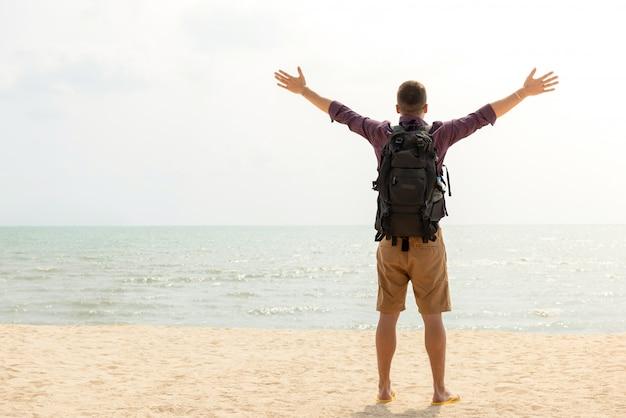 Gelukkige toerist backpacker met open armen op het strand op zomervakantie