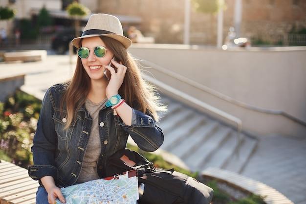 Gelukkige toerist die op telefoon spreekt die een kaart houdt die jeans draagt. zomervakantie op zijn best.