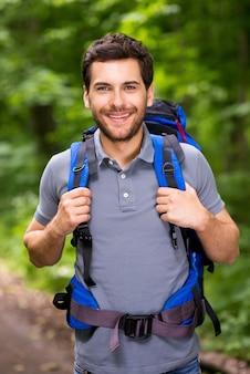 Gelukkige toerist. knappe jonge man die rugzak draagt en naar de camera kijkt met een glimlach terwijl hij in de natuur staat
