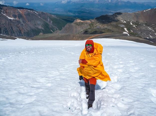 Gelukkige toerist op de top van een gletsjer in een gele aanvalsregenjas die fladdert in een sterke wind kijkt vrolijk vooruit naar de camera tegen de achtergrond van dramatische zwarte wolken boven een bergdal