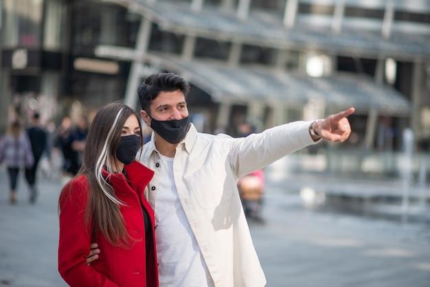 Gelukkige toeristen koppelen met covid- of coronavirusmaskers die in een stad lopen en een interessante plek aanwijzen