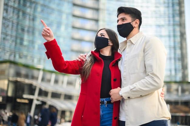 Gelukkige toeristen met covid- of coronavirusmaskers die samen in een stad wandelen en een interessante plek zien