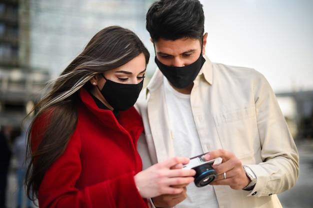 Gelukkige toeristen met covid- of coronavirusmaskers die samen in een stad wandelen en samen de foto's bekijken die samen zijn gemaakt