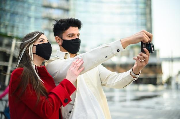 Gelukkige toeristen met covid- of coronavirusmaskers koppelen samen in een stad en fotograferen een interessante plek