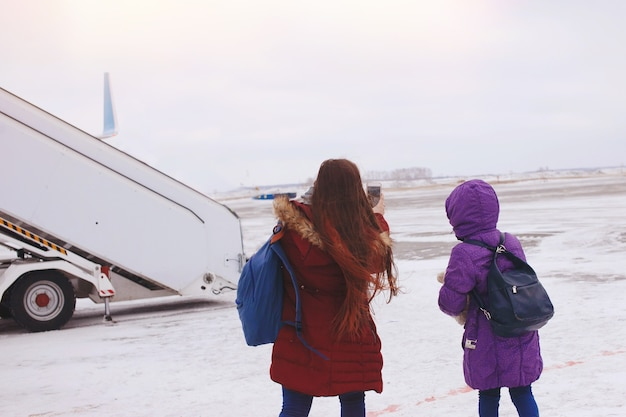 Gelukkige toeristen twee meisjes met rugzakken gaan op sneeuw naar het vliegtuig op het startveld