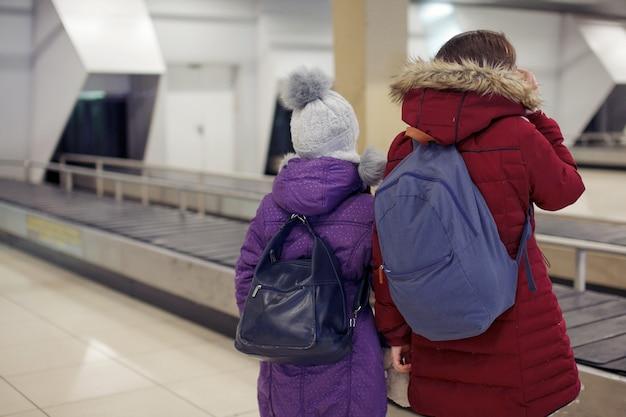 Gelukkige toeristen twee meisjes met rugzakken wachten op bagagebezorging in de buurt van de luchthaventransportband