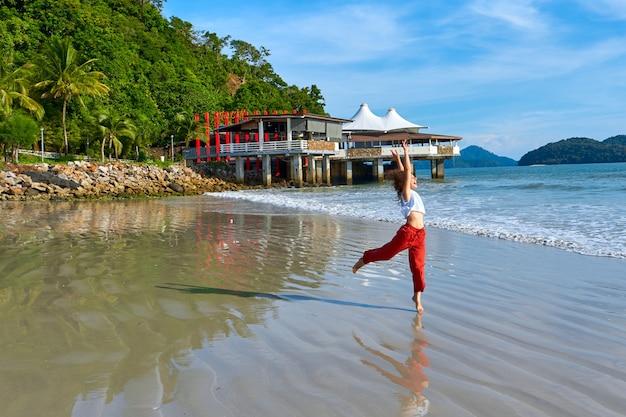 Gelukkige toeristenvrouw geniet van reizen op het centrale strand van het tropische eiland langkawi.