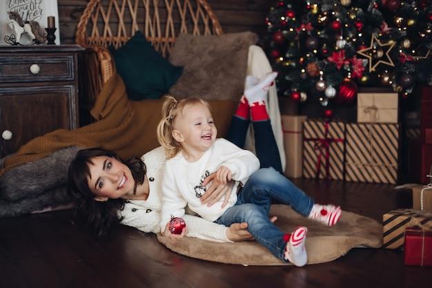 Gelukkige toevallige jonge moeder leuke glimlachende dochter die pret hebben bij het volledige schot van de kerstboom als achtergrond. prachtige familie die liefde en positieve emotie voelt en geniet van kerstversiering omringd door sneeuwvlokken