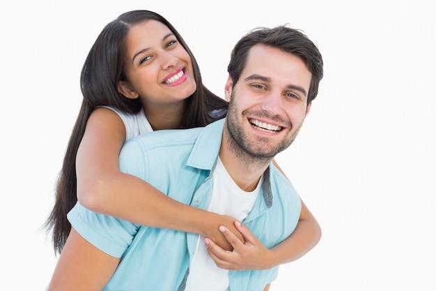 Gelukkige toevallige mens die mooi meisje op de rug een piggy geeft