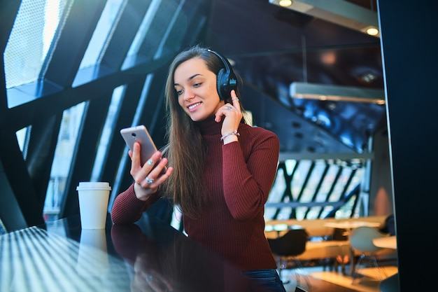 Gelukkige toevallige vrouw met zwarte draadloze hoofdtelefoons houdt mobiele telefoon en geniet van muziek. moderne mensen met een audiomobiliteit levensstijl