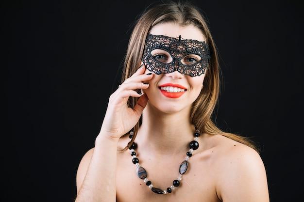 Gelukkige topless vrouw die het masker van maskeradecarnaval over zwarte achtergrond draagt