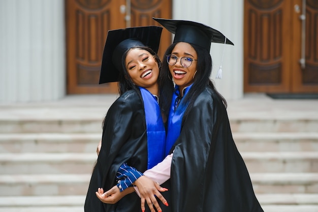 Gelukkige twee internationale studenten. afstuderen student aanvang universitair certificaat succes degree concept.