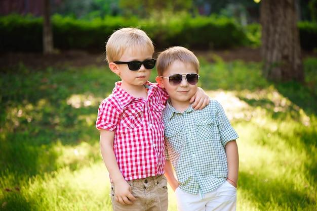 Gelukkige twee jonge geitjesvrienden in openlucht in zonnebril