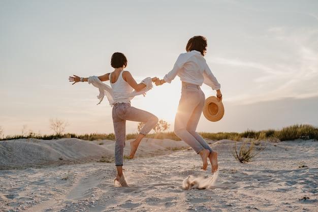 Gelukkige twee jonge vrouwen die pret hebben op het zonsondergangstrand, homo lesbische liefde romantiek