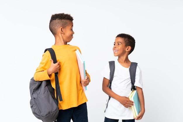 Gelukkige twee jongens afrikaanse amerikaanse studenten over geïsoleerd wit