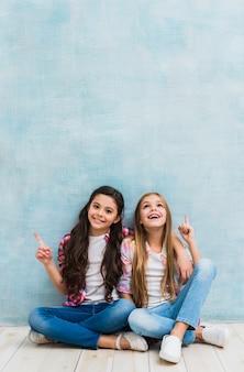 Gelukkige twee meisjes die voor blauwe muur zitten die hun vinger naar omhoog richten
