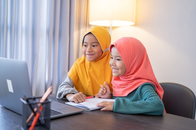 Gelukkige twee moslimkinderen die hoofdsjaal dragen die glimlachen tijdens het gebruik van laptopcomputer thuis