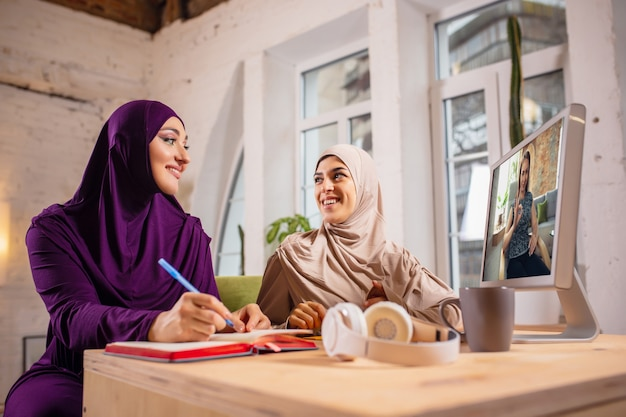 Gelukkige twee moslimvrouwen thuis tijdens de les, studeren in de buurt van computer, online onderwijs