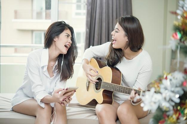 Gelukkige twee vrienden die gitaar spelen en op bed zingen.