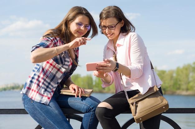 Gelukkige twee vrouwelijke vrienden die op foto's letten