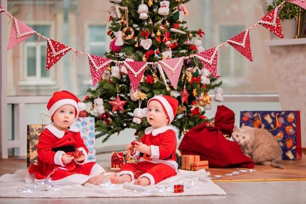 Gelukkige tweelingbaby's verkleed als kerstman zitten bij de kerstboom thuis in de woonkamer