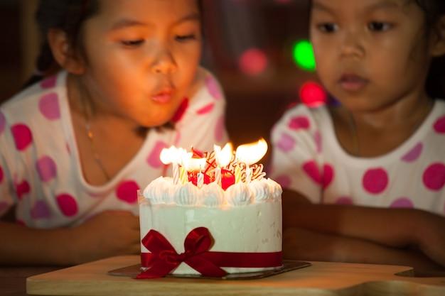 Gelukkige tweelingen die hun verjaardag vieren en samen kaarsen blazen