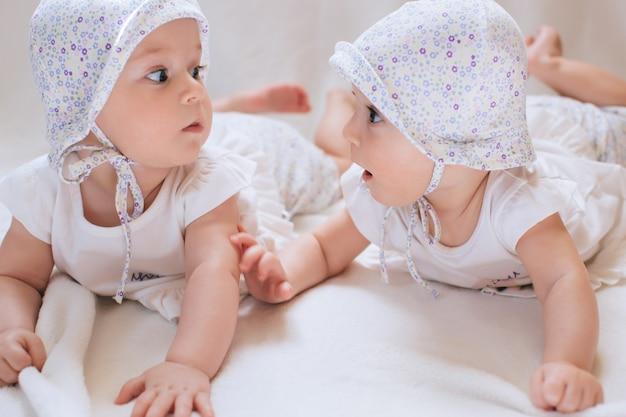 Gelukkige tweelingzusjes thuis op bed