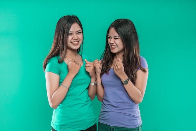 Gelukkige uitdrukking van aziatische tweelingen met gebalde vuisten op groene achtergrond