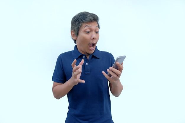 Gelukkige uitdrukking van de mens terwijl hij naar het telefoonscherm kijkt
