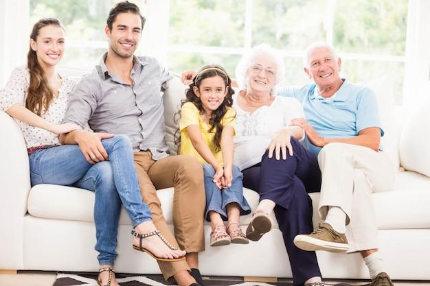 Gelukkige uitgebreide familie die thuis glimlacht