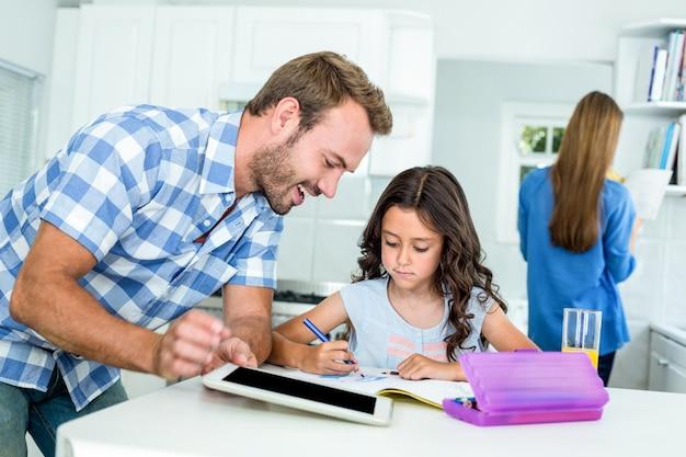 Gelukkige vader bijwonende dochter thuis in huiswerk