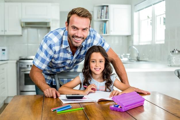 Gelukkige vader die dochter met huiswerk in keuken helpt