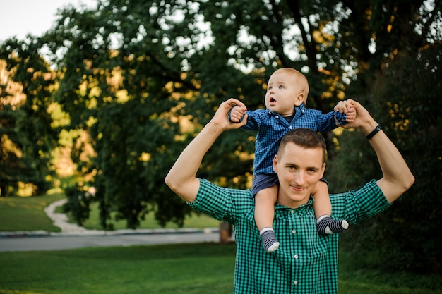 Gelukkige vader die een babyjongen houdt gekleed in het geruite overhemd op de schouders