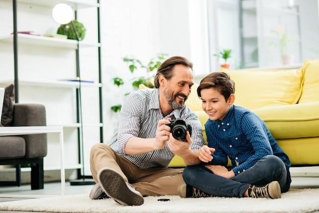 Gelukkige vader die een moderne camera vasthoudt en met een glimlach naar zijn zoon kijkt terwijl hij met hem op het tapijt in de woonkamer zit