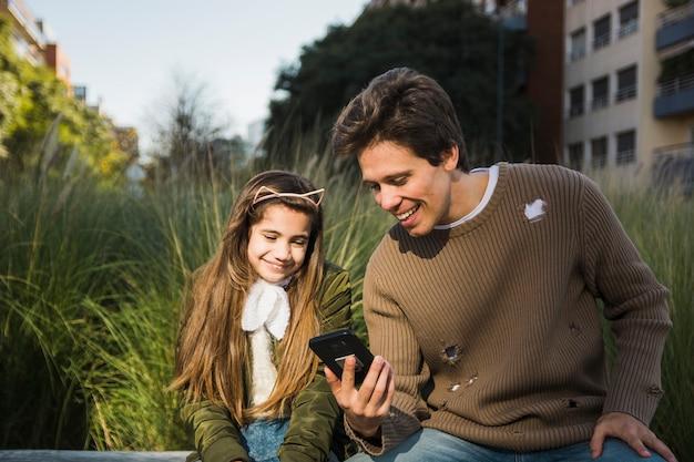 Gelukkige vader die iets toont aan zijn dochter op mobiele telefoon