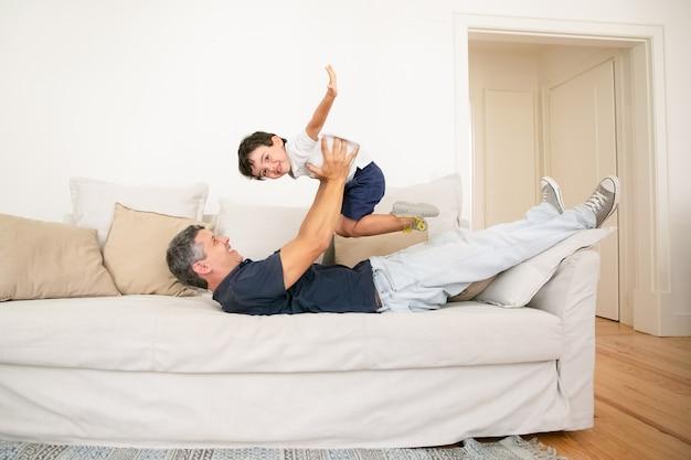 Gelukkige vader die op bank ligt en met zoon speelt.