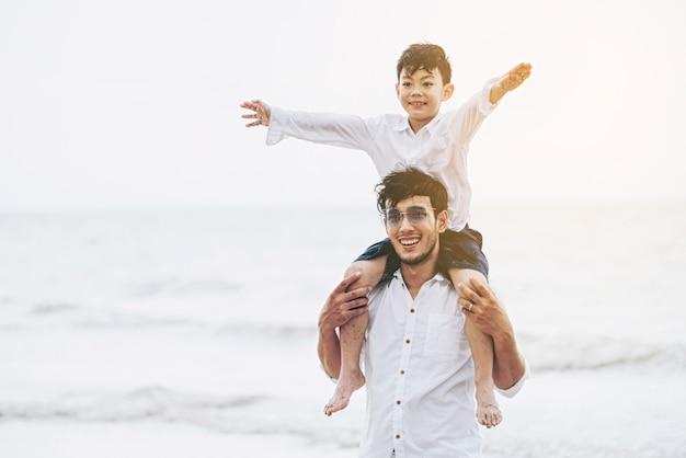 Gelukkige vader die zijn zoon op de hals vervoert.