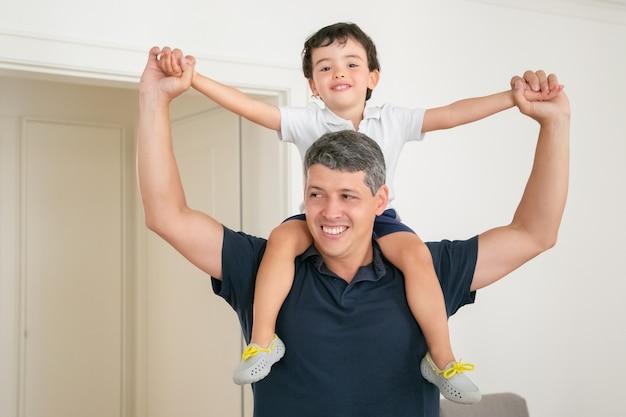 Gelukkige vader die zijn zoon op schouders houdt en handen spreidt.