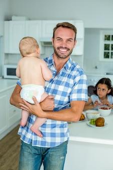 Gelukkige vader dragende zoon met dochter die ontbijt heeft