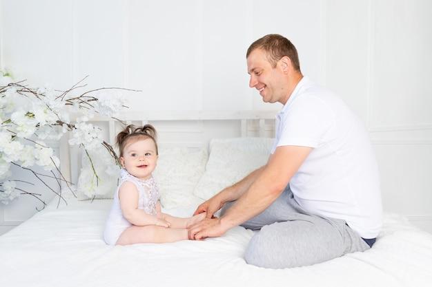 Gelukkige vader en babydochter die thuis op een wit bed praten of spelen, familie