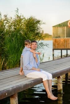 Gelukkige vader en de zoon zitten op een pier aan de oever van het meer