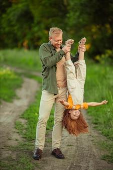 Gelukkige vader en dochter die plezier hebben tijdens een wandeling in het park