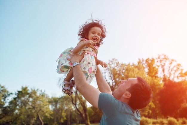 Gelukkige vader en dochter die samen in openlucht lachen