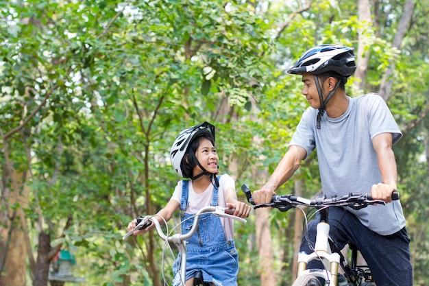 Gelukkige vader en dochter fietsen in het park