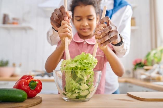 Gelukkige vader en dochter kokende salade bij het ontbijt. glimlachende familie eet 's ochtends in de keuken. vader voedt vrouwelijk kind, goede relatie