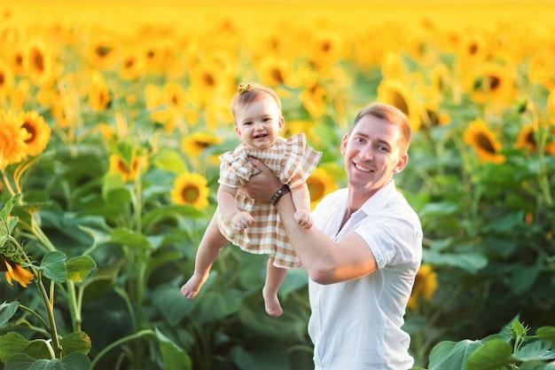 Gelukkige vader en dochter spelen buiten onder de bloeiende zonnebloemen onder de stralen van de zonsondergang