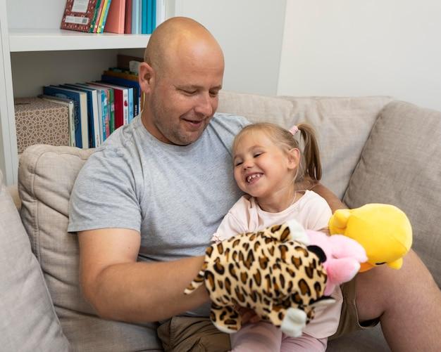 Gelukkige vader en dochter spelen met poppen